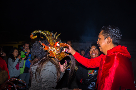 Quito, Ecuador - May 27, 2015: An unidentified people wearing a red jacket while the woman is using a devil mask in the diablada Editorial
