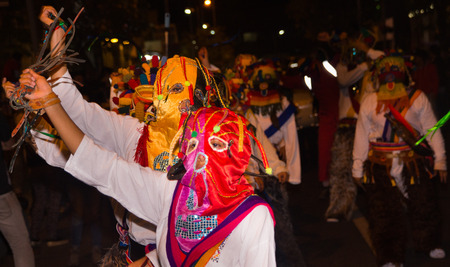 Quito, Ecuador - february 02, 2016: An unidentified man dressed up participating in the Diablada, with a colorful mask in his head while he is dancing in the streets Editorial