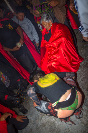 Quito, Ecuador - May 27, 2015: Close up of an unidentified man dressed up a silly clothes while an old woman is sitting in a chair wearing a red cap in the diablada