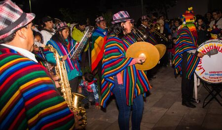 Quito, Ecuador - february 02, 2016: An unidentified people dressed up participating in the Diablada, a man with a colorful mask in his head and others playing musical instruments