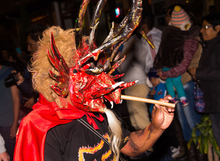 Quito, Ecuador - february 02, 2016: An unidentified man dressed up participating in the Diablada, with a demon mask in his head with a stick in his hand Editorial