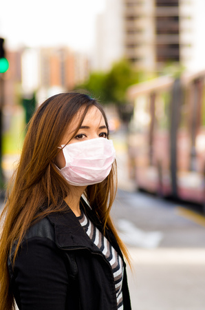 air traffic: Happy beautiful young woman wearing a protective mask on the street in the city with air pollution with a blurred bus behind, city background Stock Photo