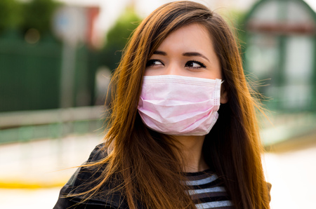 Close up of young woman with protective mask on the street in the city with air pollution, city background