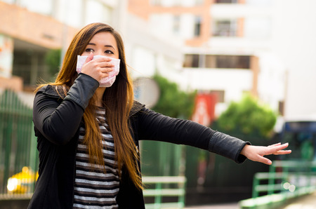 Young woman holding his protective mask with her hand on the street in the city with air pollution, asking for a taxi, city background