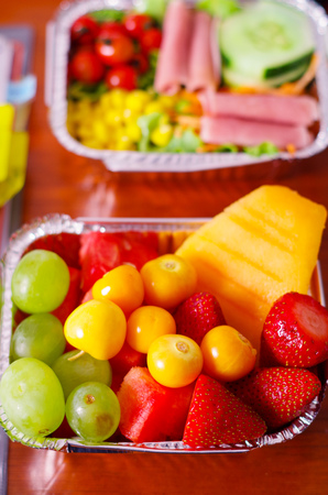 aluminium: Close up of a delicious fruit salad and blurred mediterranean-Style fresh salad with hamon on aluminium box on wooden table Stock Photo