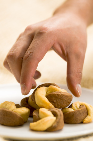 Man use his hand to take a deliciousTurkish homemade savory cookies, tuzlu kurabiye