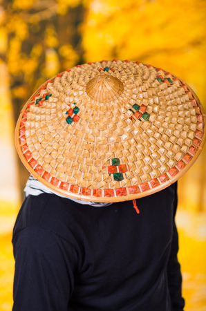 sickle: Portrait of a handsome hispanic young business guy wearing an asian conical hat and hiding his face with the hat, in autum background