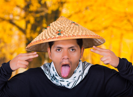 sacar la lengua: Close up of a handsome hispanic young business guy wearing an asian conical hat doing a silly face and take out the tongue in autum background Foto de archivo