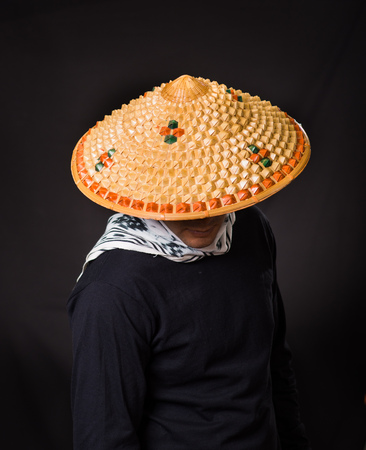 sickle: Portrait of a handsome hispanic young business guy wearing an asian conical hat and hiding his face with the hat, in black background