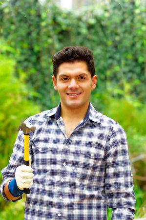 Atractive man wearing casual clothes holding a hammer in a forest background