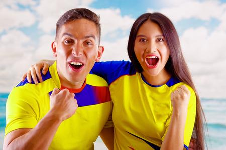 Jonge Ecuadorian paar dragen officiele Marathon voetbal shirt staande camera, zeer verloofde lichaamstaal kijken spel met grote enthousiasme, blauwe hemel en wolken achtergrond