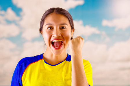 Young ecuadorian woman wearing official Marathon football shirt standing facing camera, very engaged body language watching game with great enthusiasm, blue sky and clouds background
