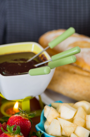 Delicious chocolate fondue with fresh fruits inside of bowls on wooden table