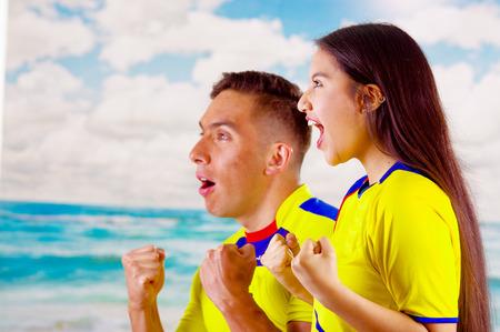 Giovane coppia ecuadoriana indossa camicia ufficiale di maratona di calcio in piedi di fronte alla fotocamera, molto impegnato lingua del corpo guardando gioco con grande entusiasmo, cielo blu e nuvole sfondo
