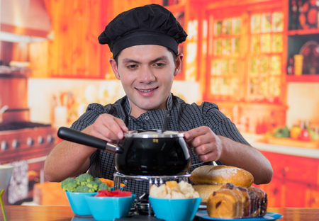 Handsome young cheff preparing a gourmet Swiss fondue dinner with assorted cheeses and a heated pot of cheese fondue and some vegetable as, broccoli, carrot and red pepper and pieces of bread inside of bowls on wooden table in kitchen background Stock Photo