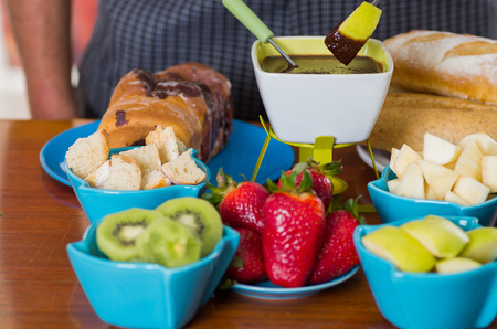 Delicious apple in a metal stick covered with chocolate fondue inside of a white bowl with assorted fruits as, strawberry, pear, kiwi, apple and pieces of bread in bowls on wooden table