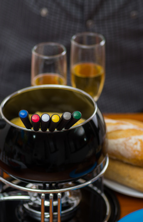 white wine: Gourmet Swiss fondue dinner with assorted cheeses and a heated pot of cheese fondue with colorful forks dipping inside of the pot, with white wines cups behind on a wooden table