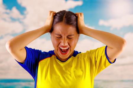 Junge ecuadorianische Frau trägt offizielle Marathon Fußball-Shirt stehende Kamera, sehr engagierte Körper Sprache beobachten Spiel mit großer Begeisterung, blauer Himmel und Wolken Hintergrund Standard-Bild