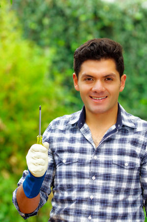 Attractive smiling young builder holding a screwdriver wearing job gloves