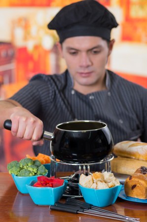 Young cheff preparing a gourmet Swiss fondue dinner with assorted cheeses and a heated pot of cheese fondue and some vegetable as, broccoli, carrot and red pepper and pieces of bread inside of bowls on wooden table in kitchen background