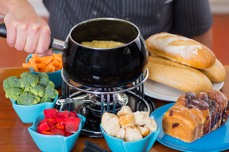 Close up of cheff preparing a gourmet Swiss fondue dinner with assorted cheeses and a heated pot of cheese fondue and some vegetable as, broccoli, carrot and red pepper and pieces of bread inside of bowls on wooden table