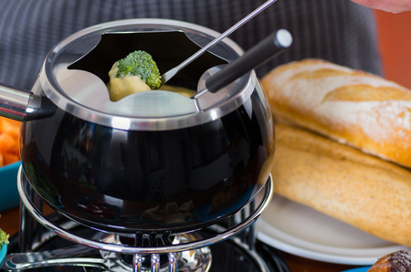 white wine: Gourmet Swiss fondue dinner with assorted cheeses and a heated pot of cheese fondue, man holding with a fork dipping a piece of broccoli covered with cheese, with a piece of bread over a white plate on wooden table Stock Photo