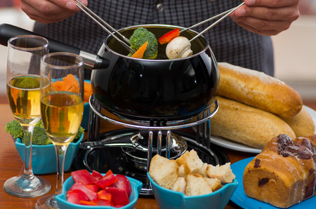 white wine: Close up of a gourmet Swiss fondue dinner with assorted cheeses and a heated pot of cheese fondue, man holding with a fork dipping a piece of bread, broccoli and red pepper covered with cheese and white wines cups on wooden table