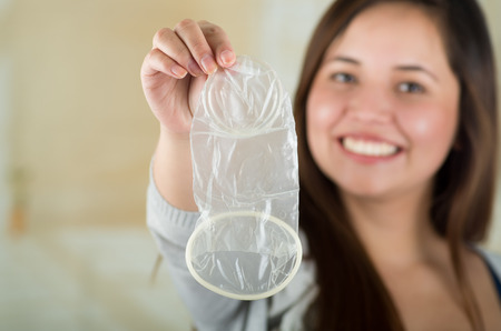 Mirroned young beautiful girl holding an open female condom, safe sex concept. Protection against AIDS and birth control