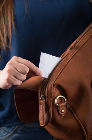 The hand of a young woman pulling a condom to prevent pregnancy from her brown purse pocket