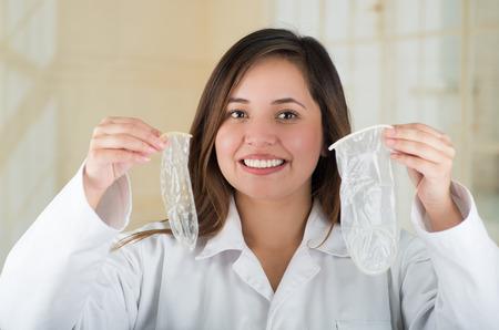 Jonge mooie arts die een open vrouwelijk condoom in één hand en een open mannelijk condon in haar andere hand, veilig geslachtsconcept houdt