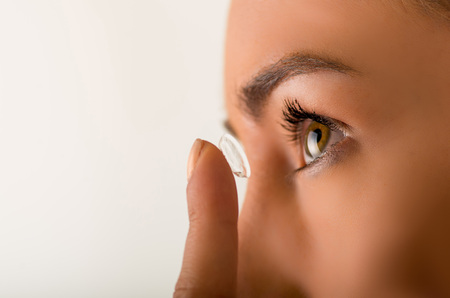 shortsighted: Close up of a young woman putting contact lens in her eye close up