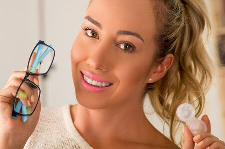 Smiling young blonde woman holding contact lens case on hand and holding in her other hand a blue glasses on blurred background., eyesight and eyecare concept Stock Photo