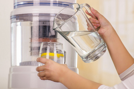 Close up of a woman holding a glass of water in one hand and a pitcher of water in her other hand, with a filter system of water purifier on a kitchen background