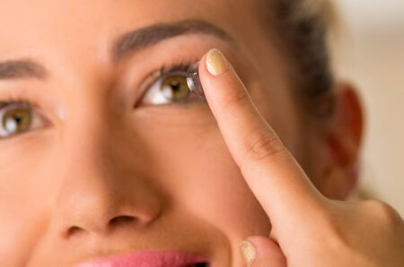 shortsighted: Young woman putting contact lens in her eye close up Stock Photo