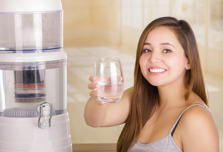 Beautiful smiling woman holding a glass of water, with a filter system of water purifier on a kitchen background