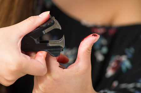 Close up of a woman injured her finger using a black staple puller