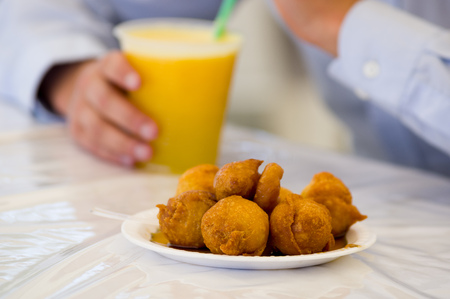 Homemade fritters with sugar and its ingredients with a blurred orange glass of juice behind Stock Photo