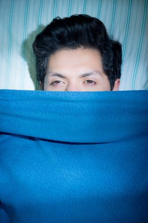 Gros plan d'un beau jeune homme au lit les yeux ouverts, souffrant d'insomnie et de troubles du sommeil pensant à son problème, recouvert la moitié de son visage d'une couverture bleue