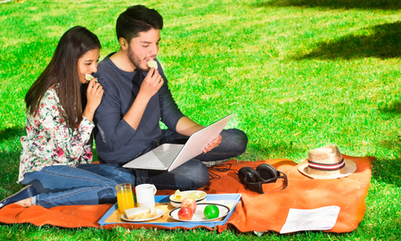 Young happy couple enjoying picnic in park and eating a potato chips while they are watching something in his computer