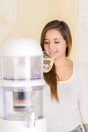 Beautiful woman drinking a glass of water with a filter system of water purifier on a kitchen background