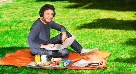 Young happy man enjoying picnic in park while he uses his computer wearing a headphones Stock Photo