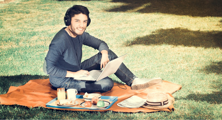 Young happy man enjoying picnic in park while he uses his computer wearing a headphones, vintage effect