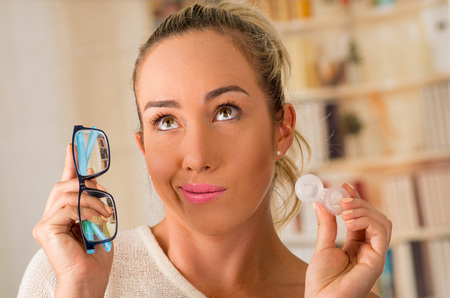 Young blonde woman holding contact lens case on hand and holding in her other hand a blue glasses on blurred background., eyesight and eyecare concept