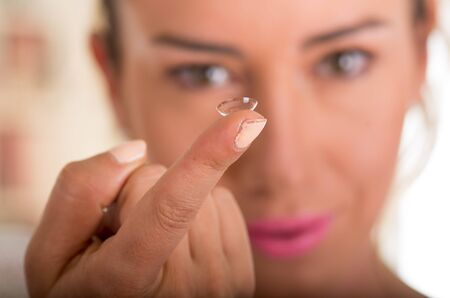 Young woman holding contact lens on finger in front of her face on white background., eyesight and eyecare concept