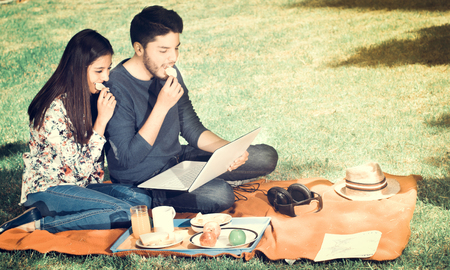 they are watching: Young happy couple enjoying picnic in park and eating a potato chips while they are watching something in his computer, vintage effect Stock Photo