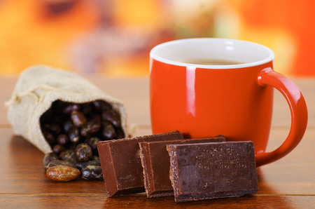 Dry cocoa bean in a small sack and a cup of chocolate over a wooden background