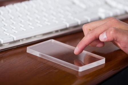 木製のテーブルに未来的な透明なスマート フォンを使用している人