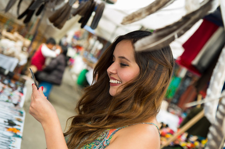 Beautiful smiling woman holding something in her hand in the andean traditional clothing and handicrafts with a blurred feather in front, market background