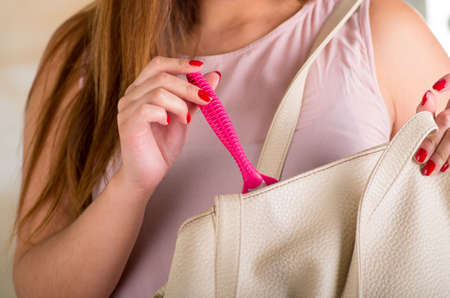 woman in bath: Close up of a young woman keeping a shaver inside of her purse with a bath background