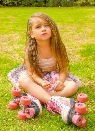 Little girl preschool sitting on backyard, wearing her roller skates and crossing her legs, in a garden background